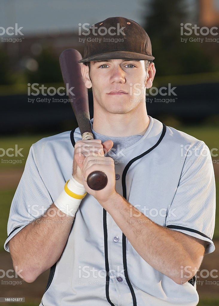 Baseball player poses for portrait with bat over shoulder stock photo