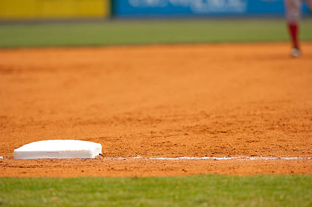 baseball player running to third base on baseball field during baseball game - spring training stock photos and pictures