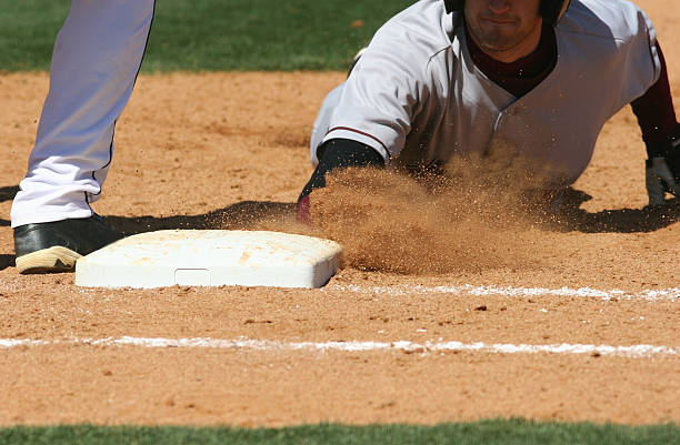 Baseball player sliding into base stock photo