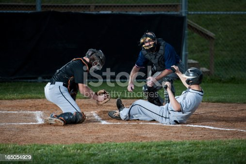 Baseball Player Slides Into Home Plate. Tightly time sequenced series as Umpire watches the action very intently, then readies his hand signal, then makes the call!