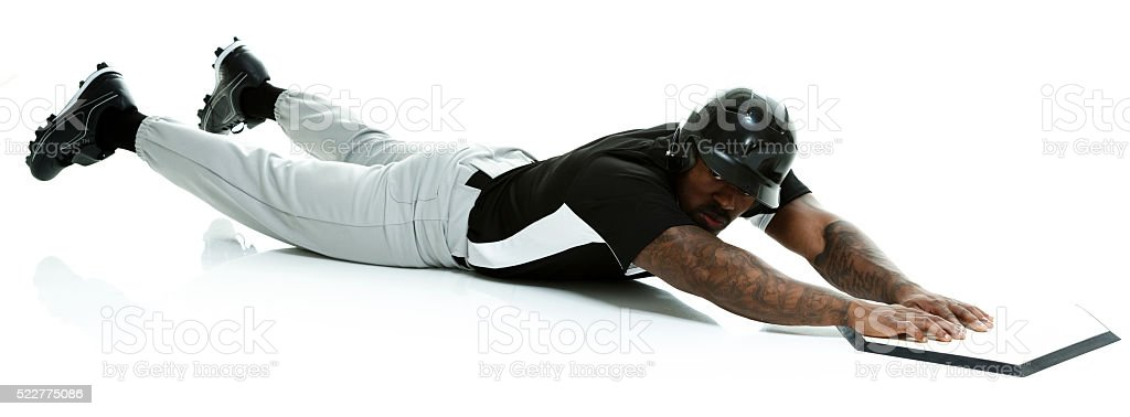 Baseball player sliding to base stock photo