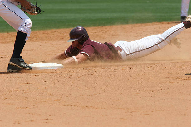 A baseball player sliding to the plate a baseball player sliding infield stock pictures, royalty-free photos & images