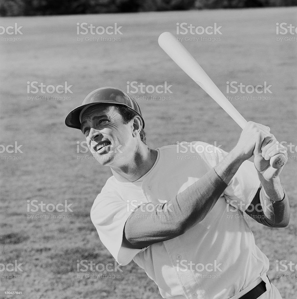 Baseball player swinging baseball bat stock photo