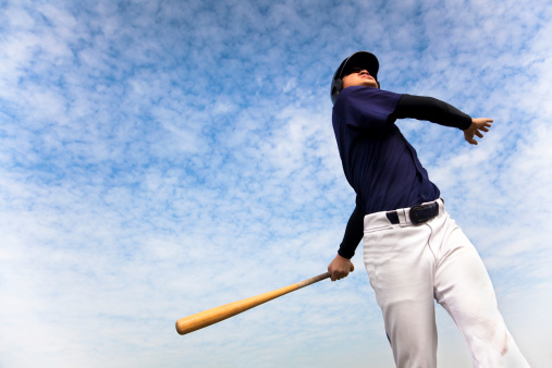 Baseball Player Taking A Swing With Cloud Background Stock Photo - Download Image Now