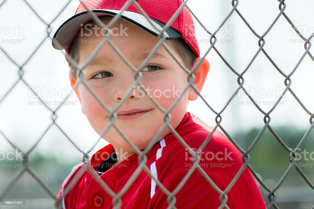 Baseball player wearing uniform sitting in dugout stock photo