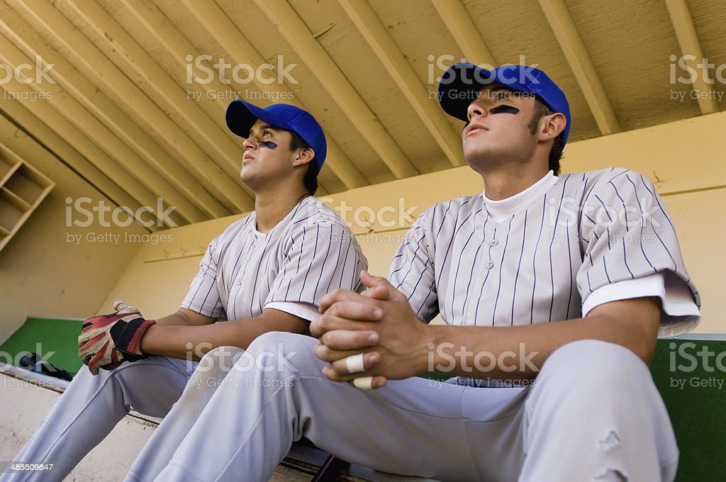 Baseball Players in Dugout Watching Game stock photo