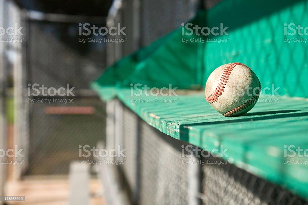 A worn baseball in a dugout