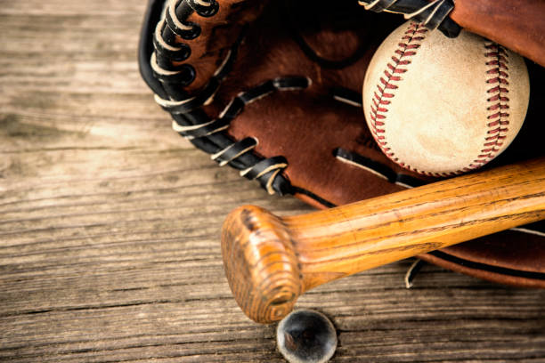 baseball season is here.  bat, glove and ball on dugout bench. - spring training stock photos and pictures