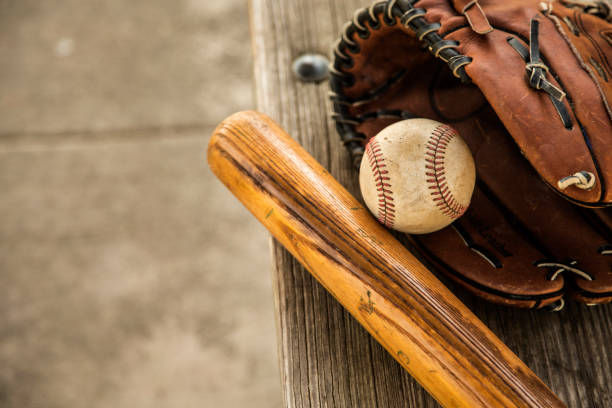 Baseball season is here.  Bat, glove and ball on dugout bench. stock photo