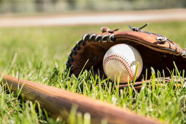Baseball season is here.  Bat, glove and ball on field. stock photo