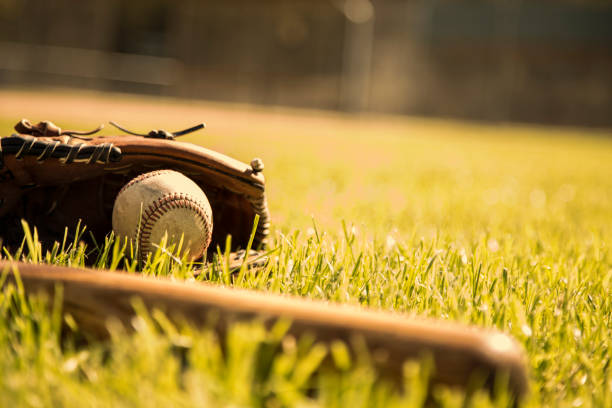 baseball season is here.  bat, glove and ball on field. - spring training stock photos and pictures