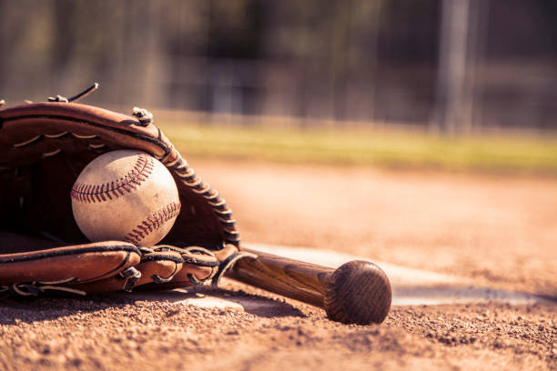 Baseball season is here.  Bat, glove and ball on home plate. Spring and summer baseball season is here.  Wooden bat, glove, and weathered ball lying on home plate in late afternoon sun.   No people.  Great background image. baseball diamond stock pictures, royalty-free photos & images