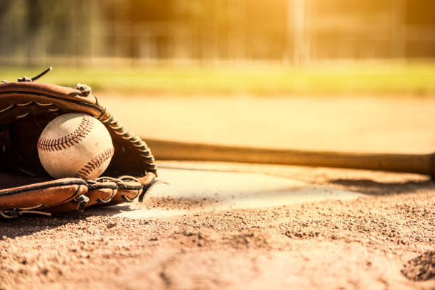 Baseball season is here.  Bat, glove and ball on home plate. stock photo