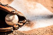 Spring and summer baseball season is here.  Wooden bat, glove, and weathered ball lying on home plate in late afternoon sun.  Dugout in background.  No people.  Great background image.