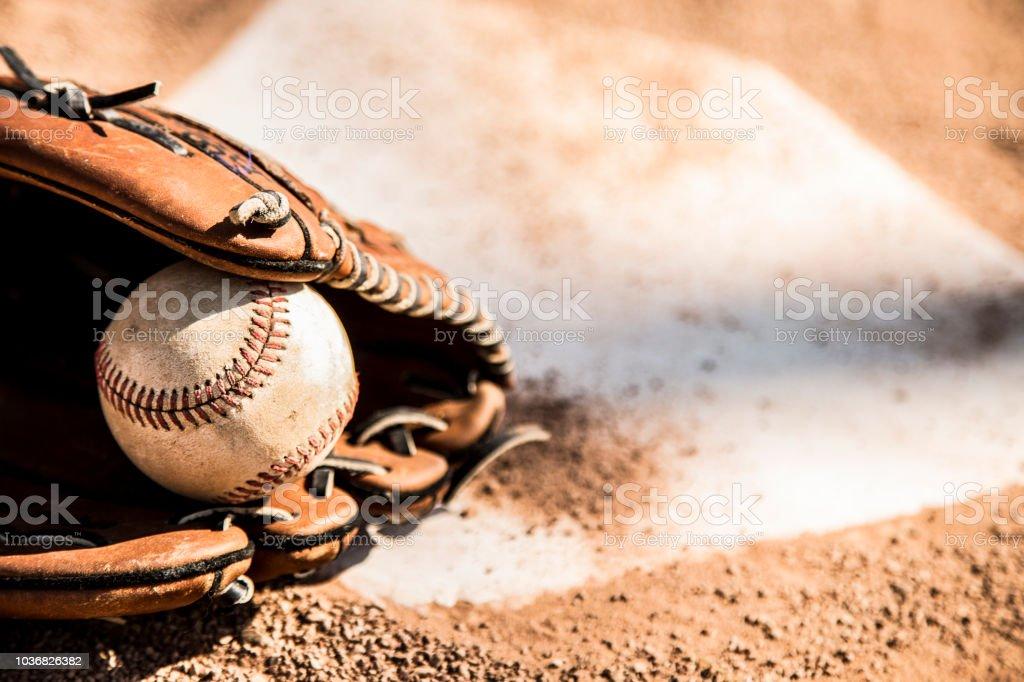 Baseball-Saison ist hier.  Handschuh und Ball auf Home-Plate. – Foto