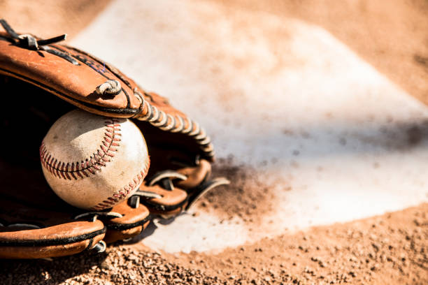 Baseball season is here.  Glove and ball on home plate. Spring and summer baseball season is here.  Wooden bat, glove, and weathered ball lying on home plate in late afternoon sun.  Dugout in background.  No people.  Great background image. baseball sport stock pictures, royalty-free photos & images