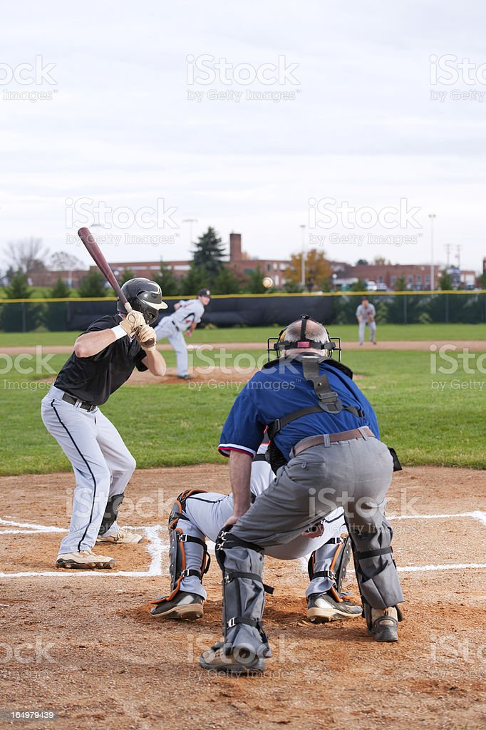Focus on the batter. Ball in mid-air about to be struck.Pitcher...