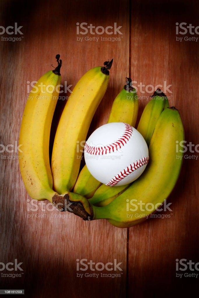 Baseball Sitting in Banana Bunch royalty-free stock photo