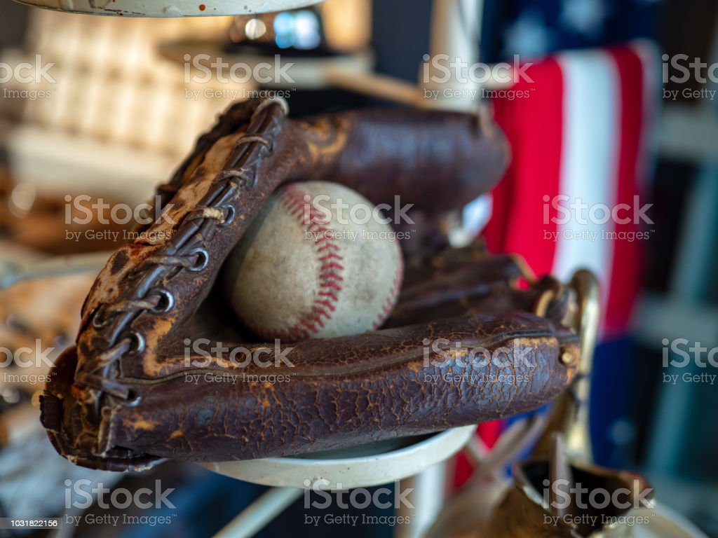 Baseball sitting in old fashioned glove with American flag in background stock photo