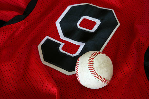 Baseball sitting on red sports jersey with black number 9