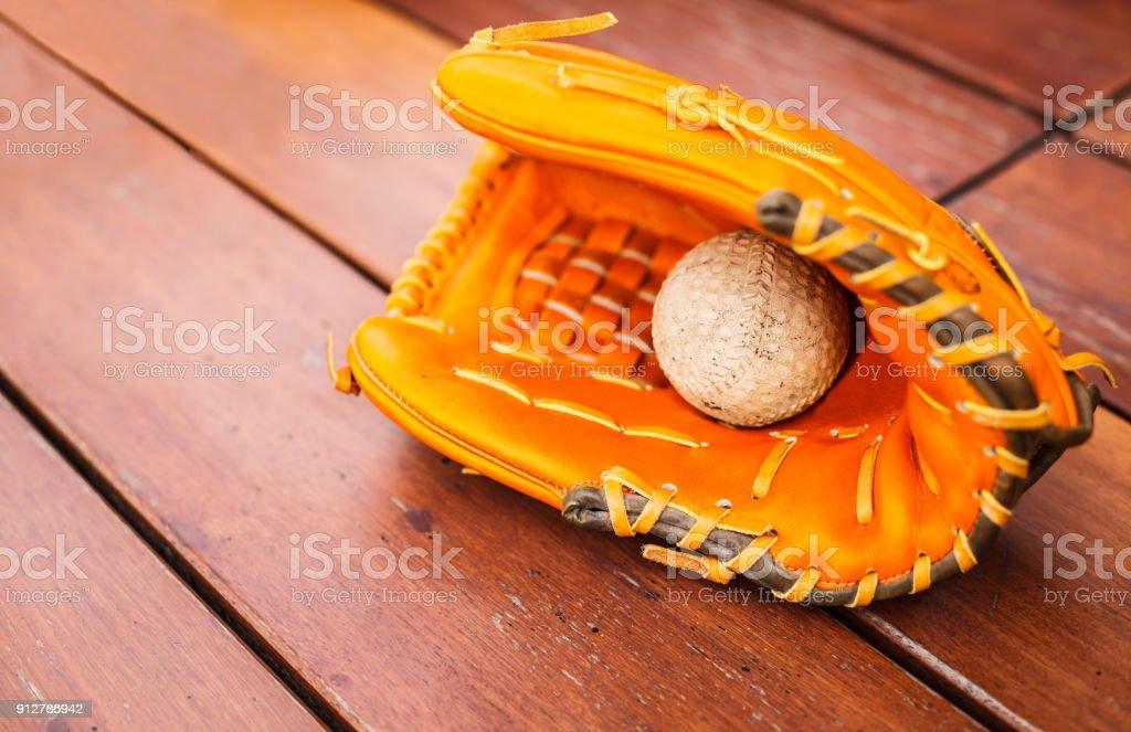 Baseball, Softball with leather mitt glove on wood table floor...