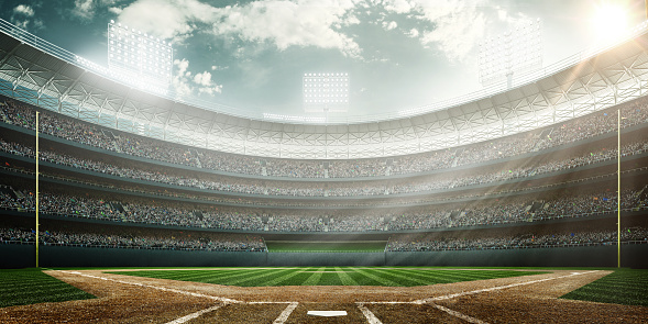 A wide angle of a outdoor baseball stadium full of spectators under a cloudy sky at midday. The image has depth of field with the focus on the foreground part of the pitch.