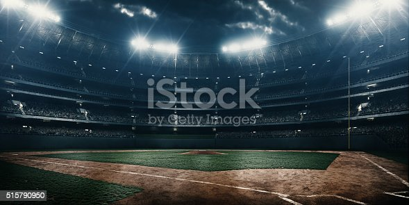 A wide angle of a outdoor baseball stadium full of spectators under a stormy night sky and rain. The image has depth of field with the focus on the foreground part of the pitch.