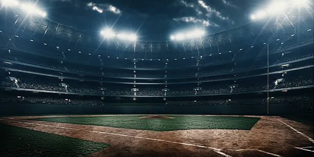 Baseball stadium A wide angle of a outdoor baseball stadium full of spectators under a stormy night sky and rain. The image has depth of field with the focus on the foreground part of the pitch. baseball sport stock pictures, royalty-free photos & images