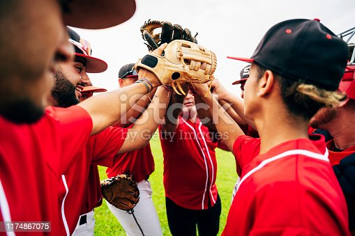 Young Hispanic baseball team and coach raising gloves for motivational high-five before game starts.