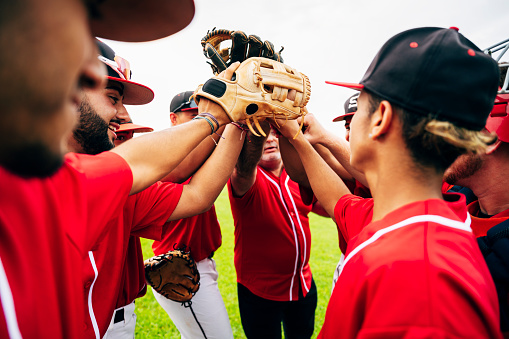 Baseball team coach and players raising gloves for high-five
