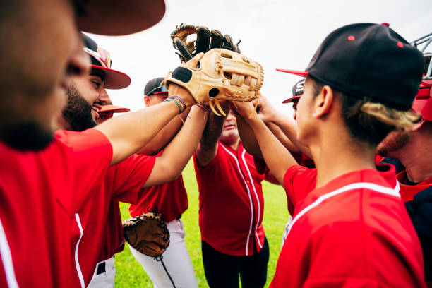 Baseball team coach and players raising gloves for high-five Young Hispanic baseball team and coach raising gloves for motivational high-five before game starts. baseball sport stock pictures, royalty-free photos & images