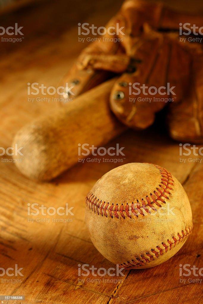 Old baseball, bat and glove. Shallow focus on ball.