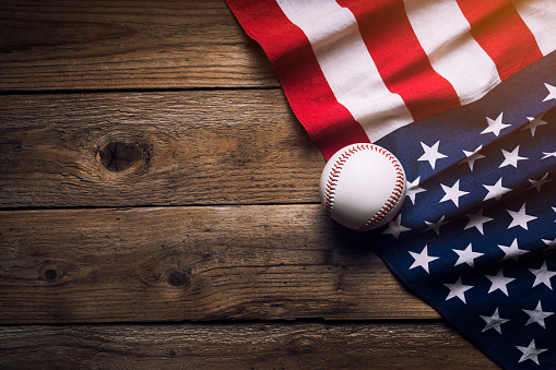 istock baseball with American flag in the background 843330732
