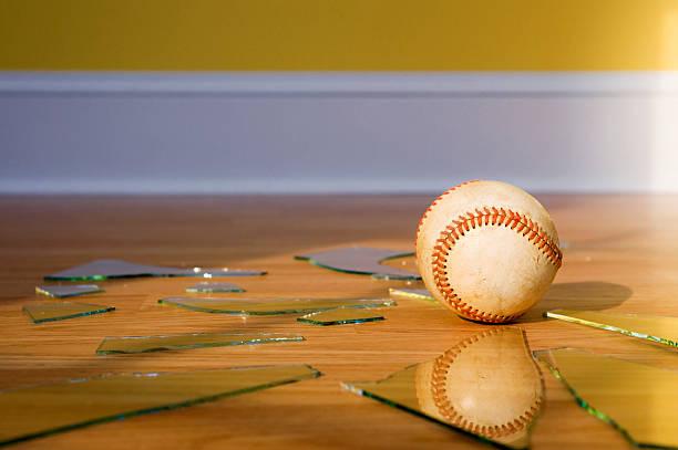 Baseball avec fenêtre en verre cassé sur le parquet - Photo