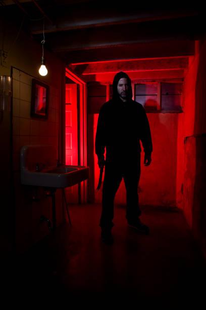 Subsolo banheiro com capuz Killer segurando assustador faca, espaço para texto - foto de acervo