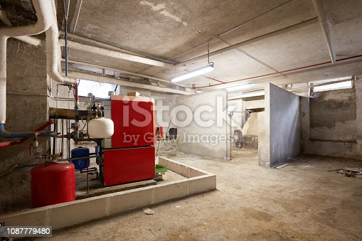 istock Basement with red heating boiler and dirty floor in old house interior 1087779480
