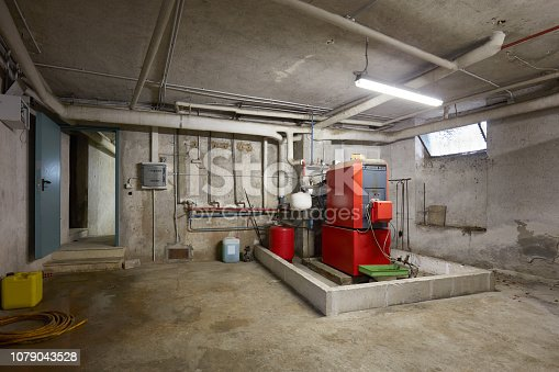 istock Basement with red heating boiler in old house interior 1079043528