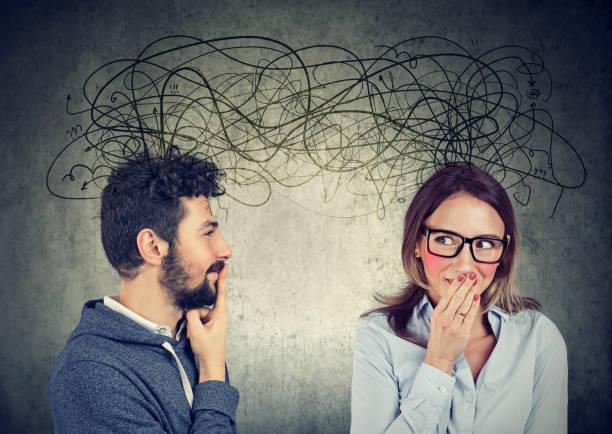 mujer tímida mirando a un hombre guapo tanto intercambiando entre sí con muchos pensamientos - foto de stock