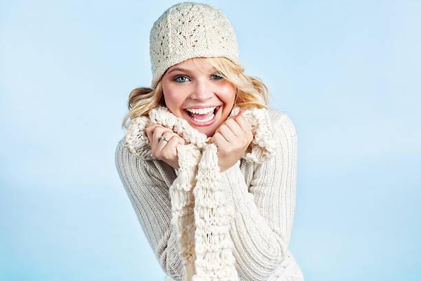 bashful junge blonde frau in weißen pullover - mützenschal stock-fotos und bilder
