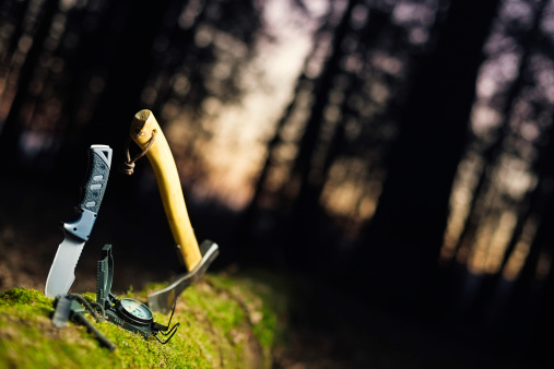 basic bushcraft tools isolated on fallen tree in the night, copy space