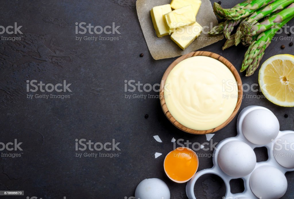 Basic french sauce hollandaise in a wooden bowl with ingredients stock photo
