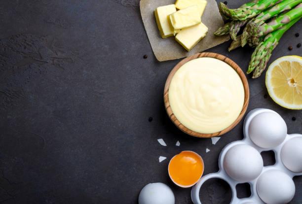 grundlegende französische sauce hollandaise in eine holzschale mit zutaten - sauce hollandaise stock-fotos und bilder