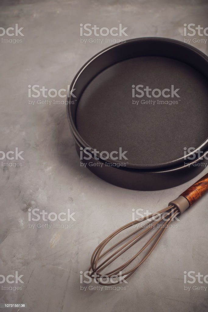 Basic kitchen utensils with cake molds on gray stone background with space for text. stock photo