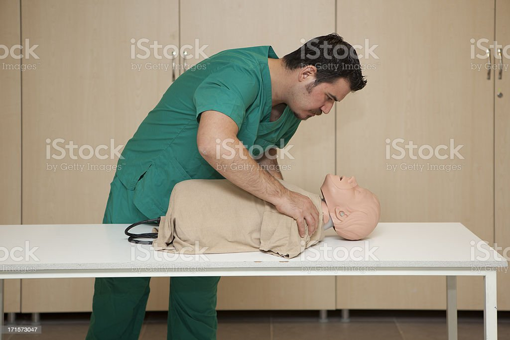 Basic life support training with a CPR Dummy-Check for consciousness royalty-free stock photo