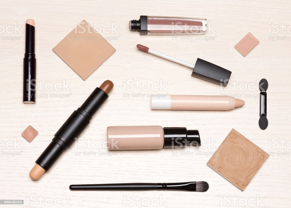 Basic makeup cosmetic products on light wood table flat lay stock photo