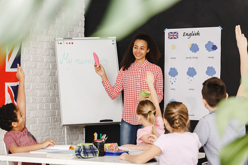 Young teacher learning kids basic words in english