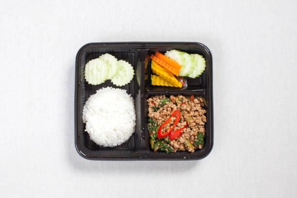 Basilikum gebratenen Reis mit Hackfleisch, in eine schwarze Plastikbox, auf eine weiße Tischdecke, Lebensmittel-Box, würzig gebratenes Schweinefleisch mit Basilikumblättern, Thai-Küche. – Foto