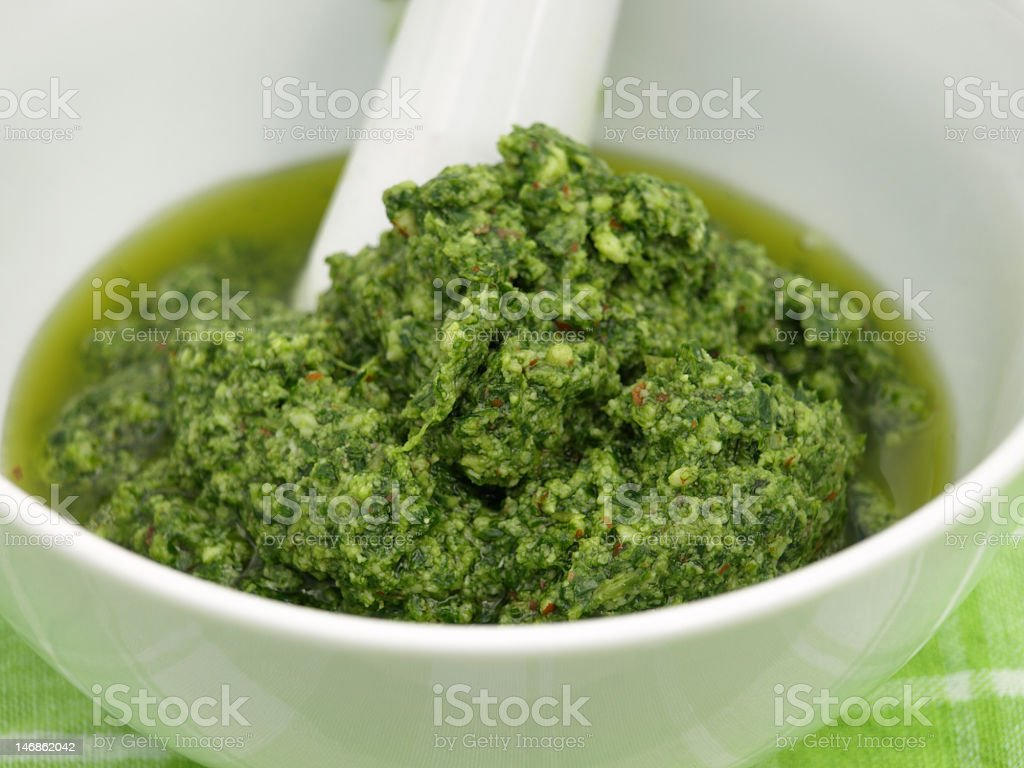 Basil pesto in a white bowl on a green tablecloth royalty-free stock photo