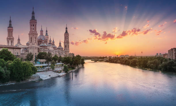 Basilica Cathedral of Our Lady of Pillar and bridge over Ebro River at sunset in Zaragoza, Aragon, Spain. Famous tourist landmark stock photo