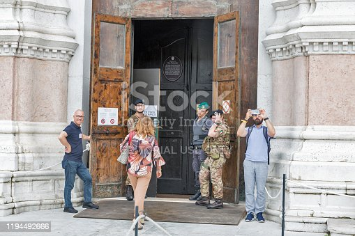 BOLOGNA, ITALY - JULY 10, 2019: People visit guarded Basilica di San Petronio in city historic center. Bologna is the capital and largest city of the Emilia-Romagna region in Northern Italy.